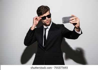 Playful macho in black classic suit and sunglasses taking selfie on smartphone, isolated over white background