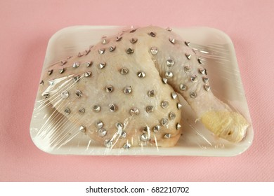 playful mash-up using a chicken thigh and punk spikes on a pink background