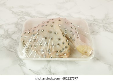 playful mash-up using a chicken thigh and punk spikes on a marble background