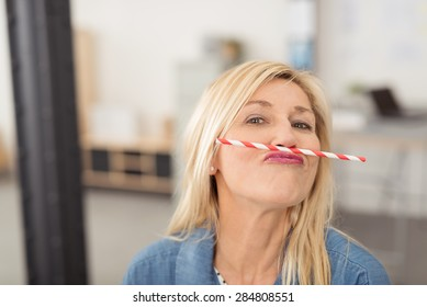 Playful middle-aged blond woman having fun balancing a straw on her upper lip while looking at the camera