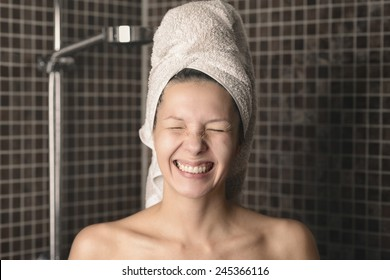 Playful mischievous naked woman with her wet hair in a towel giving the camera a big cheesy grin with her eyes closed as she stands in the bathroom, candid portrait