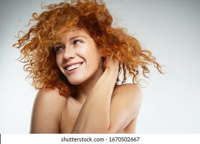 Playful mood. Charming red-haired girl keeping smile on her face while being deep in her thoughts