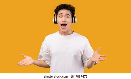 Playful Mood. Cheerful Asian Man Listening To Music In Wireless Headphones, Dancing And Spreading Hands, Posing Isolated On Orange Studio Background, Enjoying Favorite Songs, Copy Space