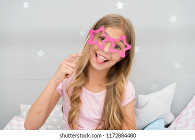Playful mood. Girl with long blonde curly hair posing with photo booth props. Pajamas party concept. Girl star shaped eyeglasses at pajamas party. Cheerful young lady posing with eyeglasses.
