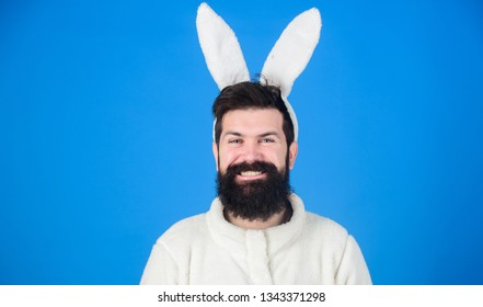 In playful mood. Man wearing long rabbit ears. Bearded man in Easter rabbit costume. Easter bunny or hare. Hipster dressed for Easter party. Easter bunny is symbol of fertility and spring, copy space.
