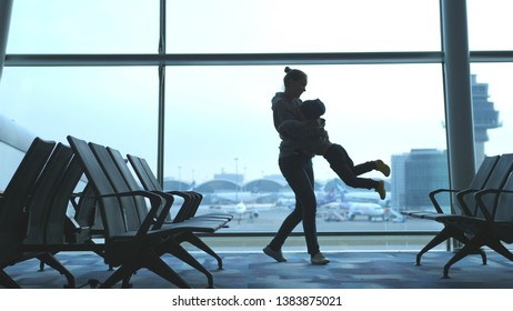 Playful mother raises her son and holds him in arms looking through window in airport.