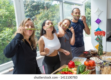 Playful people making fake moustache from asparagus. Man and women posing at camera and standing at kitchen table with fresh vegetables and window in background. Healthy cooking and friends concept.