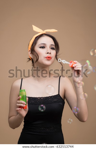 Playful pinup girl blowing party bubbles over yellow background