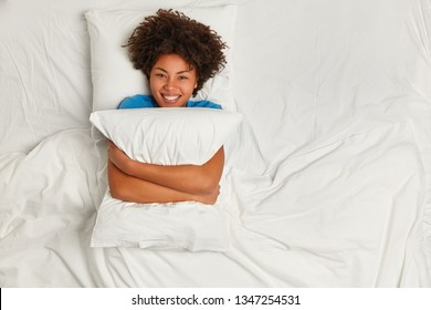 Playful pleased dark skinned woman embraces pillow, looks gladfully at camera, smiles broadly, rejoices having weekend at home, enjoys laziness and relaxation in soft bed. Waking up concept.