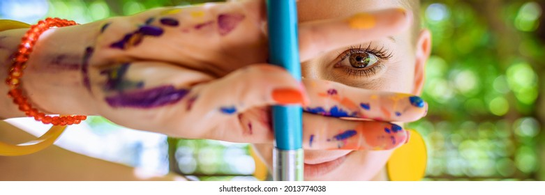 Playful portrait of a young gorgeous female painter artist, with hands covered in paint, looking and smiling at camera through her fingers. Creativity and individuality banner.