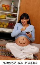 Playful pregnant woman eating chocolate cream.
