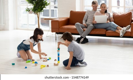 Playful preschooler boy and girl sibling sit on warm floor play with building bricks at home, young parents relax on couch watch movie on laptop, kids engaged in funny activity. Family weekend concept