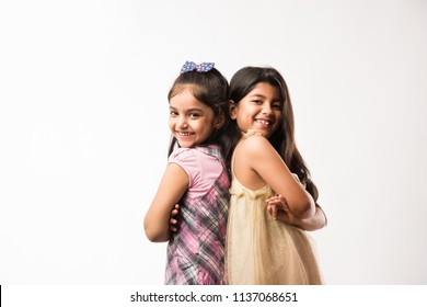 Playful and pretty Indian/asian little sisters or friends in playful mood, hugging, dancing, pushing each other. Isolated over white background