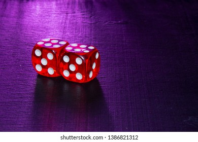 Playful red dice on a black wooden background. Purple light.