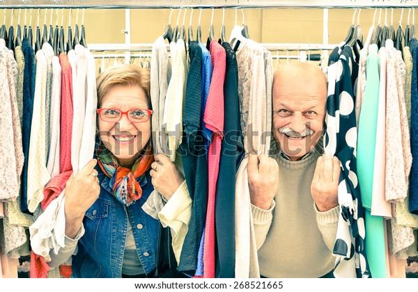 好玩的老年夫妇在弱跳蚤市场-活跃的老年人与成熟的男人和女人在老城区玩乐和购物的概念-在温暖的复古怀旧的样子快乐退休时刻