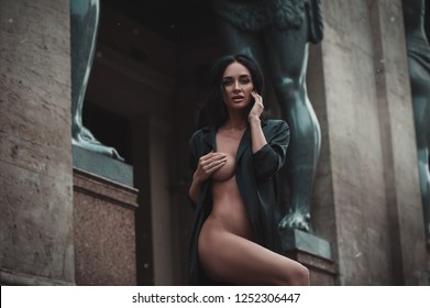 Playful sexy erotic woman in black cloak naked outdoors at Saint-Petercburg city Russia near Hermitage