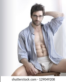 Playful sexy portrait of a handsome buff man in underwear and open business shirt with sensual expression against white