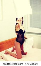 Playful sexy woman throwing a pillow during having fun in the bedroom.