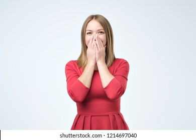 Playful shy woman hiding face laughing timid. Pretty girl is glad to receive a gift or compliment