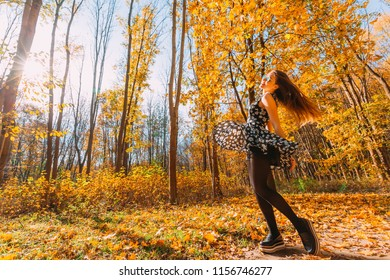 Playful slim young girl with waving glow long hair in flying gorgeous dress spinning and dancing around and having fun in the autumn park on sunny day. Photo in motion.