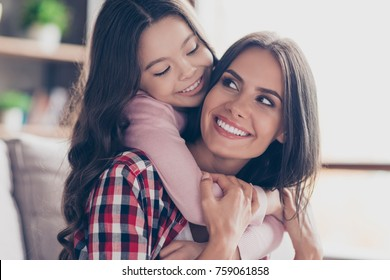 Playful small girl with long dark hair is hugging her mum's neck and looking at her with a smile, they have perfect weekends at home