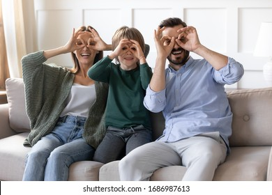 Playful small kid boy involved in family activity with smiling parents, making funny grimaces, eyewear with fingers. Overjoyed couple playing tricks fool with cute excited little child son on sofa.
