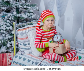 Playful smiling happy cute girl dressed in striped pajamas with gift and clock sitting in decorated New Year room at home. Christmas good mood. Lifestyle, family and holiday 2018 concept