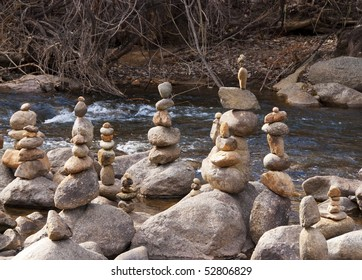 Playful stacked stones in a park amid boulders in a fresh running stream.