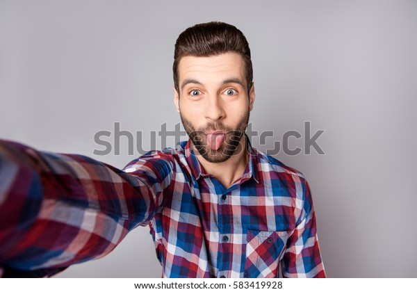 Playful stylish man isolated on gray background showing tongue and taking a selfie