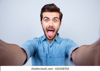 Playful stylish man on light blue background is showing his tongue and taking a selfie