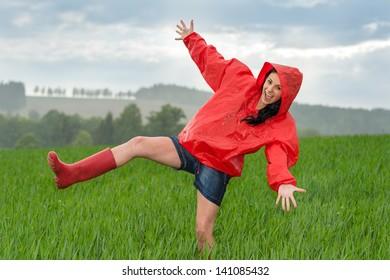 Playful teenage girl dancing in the rain on a field