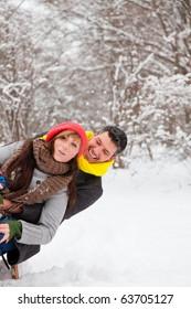 Playful winter couple sledding on sled in park