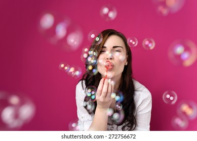 Playful woman blowing party bubbles at the camera as she celebrates a special occasion or birthday, over magenta