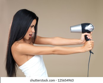 Playful woman having fun with a hairdryer holding it out in her outstretched hands pointing back at her own face isolated on beige