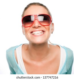 Playful woman wearing sunglasses leaning in towards the camera giving a toothy smile
