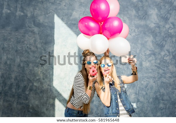 Playful women having fun with sweet donuts and baloons on the blue wall background