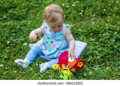 Playful young baby sitting in park on grass.