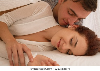 Playful young beautiful couple laying together under white linen in bed, hugging and kissing with romance, passion and desire, home interior. Lovers together in bedroom, indoors lifestyle.