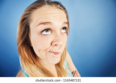 A playful young blonde makes a humorous face, looking cynical and disbelieving