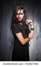 Playful young brunette wearing black clothes posing near gray wall