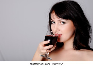 playful young charming brunette with a glass of red wine in hand