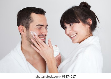 Playful young couple applying cream in the bathroom