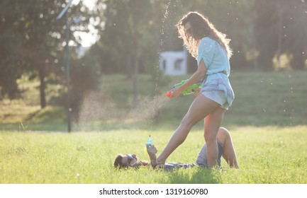 A playful young couple chasing each other and playing with water guns in a meadow ar sunset.