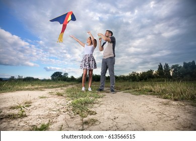Playful young couple is flying a kite on a meadow