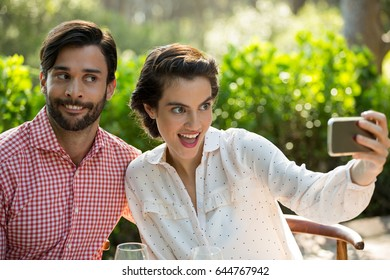 Playful young couple taking slefie through smart phone at park