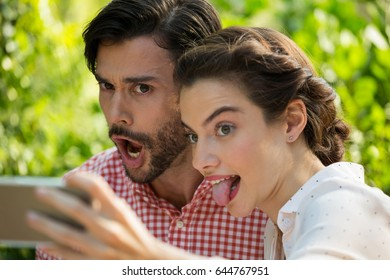 Playful young couple taking slefie through mobile phone at park
