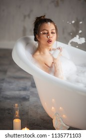 playful young female blowing air kiss with foam in bath