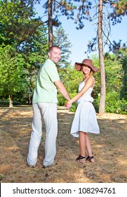 Playful young love couple having fun in forest
