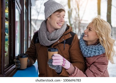 Playful young loving couple is dating outdoor. They are buying cups of coffee in shop and laughing