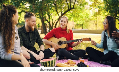 Playful young people are singing and moving hands when beautiful girl is playing the guitar during picnic in park on sunny autumn day. Fun and music concept.
